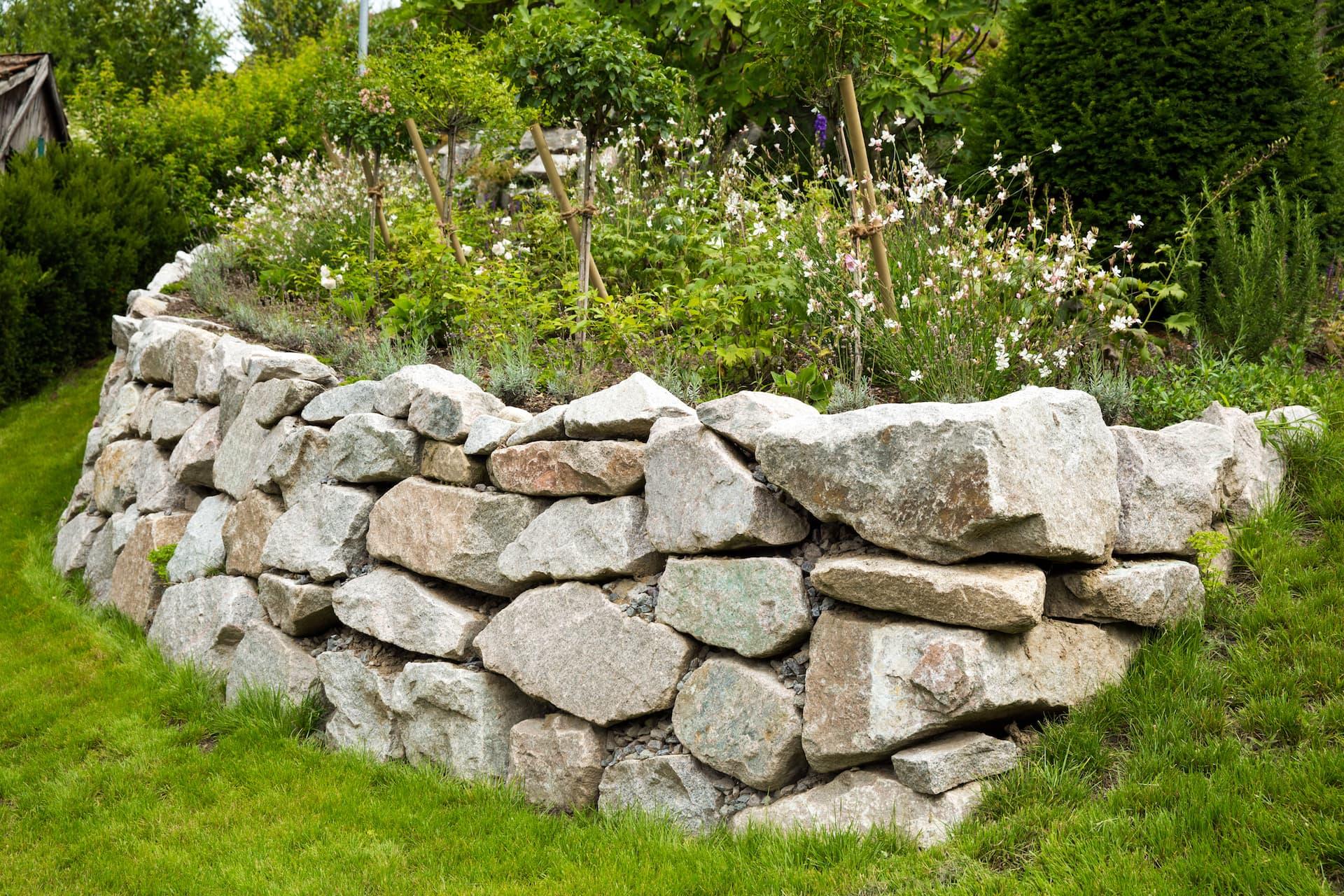 Aufschichtung einer Natursteinmauer in schwerzugänglichem Gelände