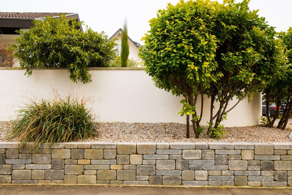 Sichtschutz aus Stein Mauerwerk verputzt mit Betonabdeckplatten.